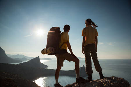 mountain valley: Tourist couple is walking a mountain and looking at sunrise above the sea