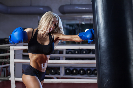 sandbag: attractive young woman making a punch on the black sandbag in blue glove Stock Photo