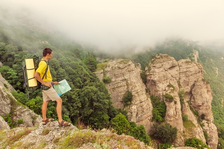 researches: Hiker on a mountain researches a way using a paper map
