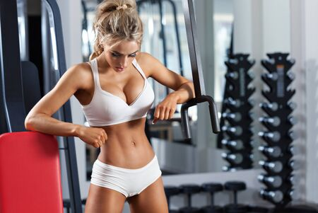 Sexy blonde woman close to lifting machine at the gym Stock Photo