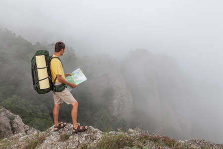 researches: Hiker researches a way using a paper map Stock Photo