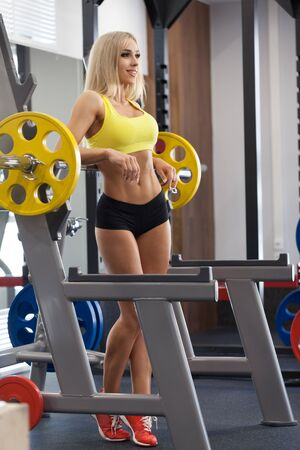 sexy blonde girl: sexy young girl resting after barbell exercises. Fitness blonde woman
