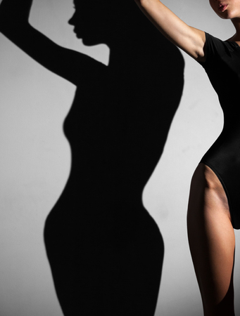 woman shadow: Body of young sportive woman with shadow on the wall