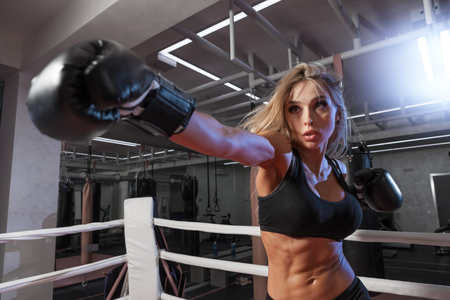 boxing match: attractive young woman making a punch on the black sandbag in blue glove Stock Photo