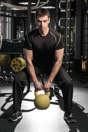 raises: Young muscular man during workout in the gym. man raises a barbell.