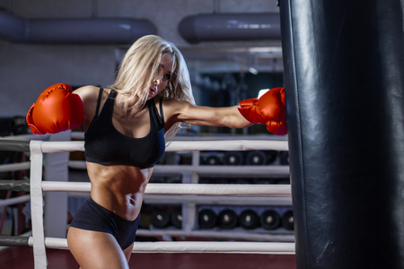 attractive young woman making a punch on the black sandbag in red glove Stock Photo