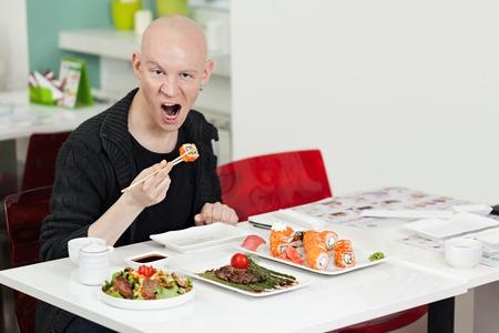 Jonge man zit op sushi bar, en het hebben van een lunch van de Japanse keuken Stockfoto