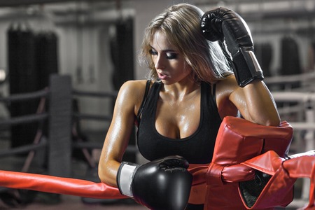 female boxing: Young tired boxer woman standing on ring and resting. Sweat wet skin.