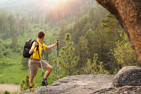 go up: Man with small backpack go up mountain and looking at sunrise Stock Photo