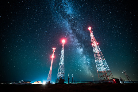 Power lines and tower against night sky with stars and milky way galaxy Stock Photo