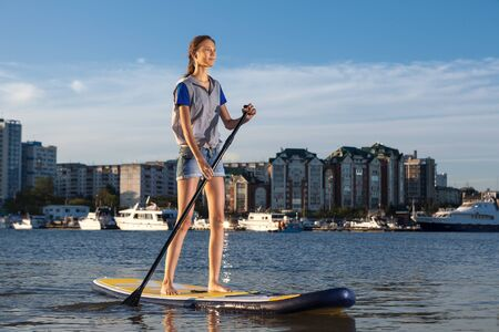sup: Young pretty woman on Stand Up Paddle Board. SUP. Shape of a sity on background Stock Photo