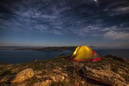 iluminated: Iluminated tent against mountain at moon night on rocks Stock Photo