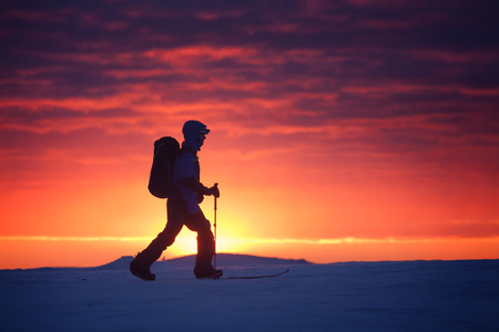 Skiers walking on the mountain against sunset