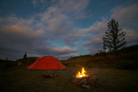 A tent and campfire under an evening sky Stock Photo