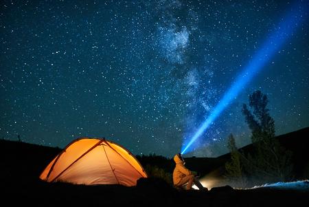 Turista de homem com lanterna perto de sua barraca do acampamento à noite.