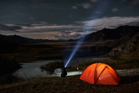 Man tourist with flashlight near his camp tent at night.