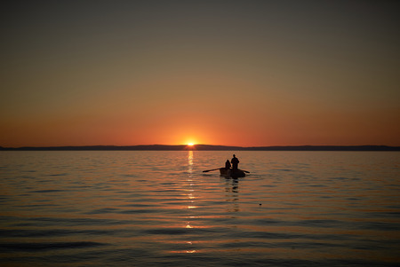 Boat in the sea with two fishermen in it, nets in the sea. Sunset or sunrise