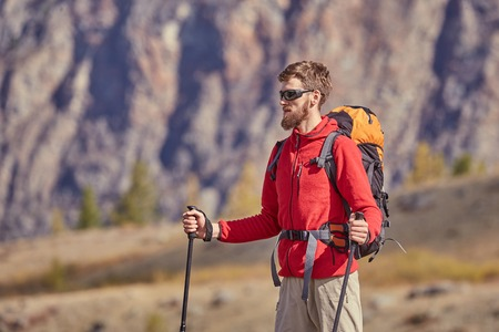 Tall backpacker with poles in hand. Stock Photo
