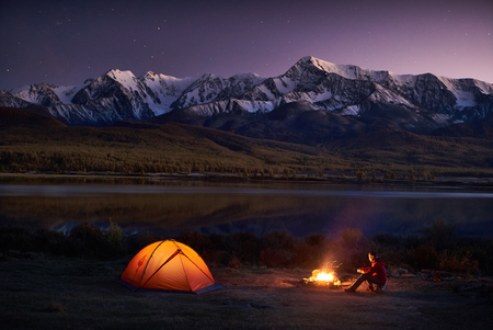 Man tourists sitting in the illuminated tent near campfire