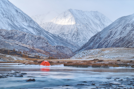 Winter or late fall in mountains, lonely camping and a river