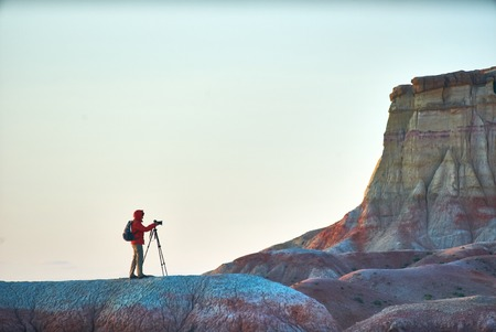 A person taking pictures in colorful Mongolian canyons. sky
