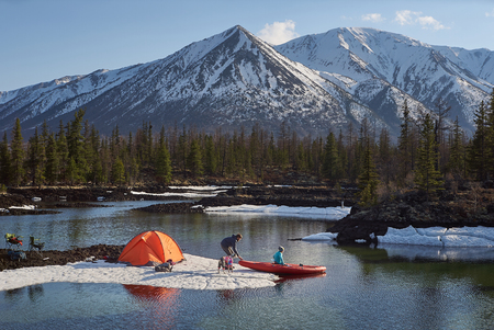 Couple man and woman in a camp at mountain terrain. Lake shore with canoe