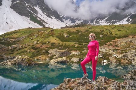 Hiking woman in red jacket stay at beautiful turquoise lake in mountains. Stock Photo