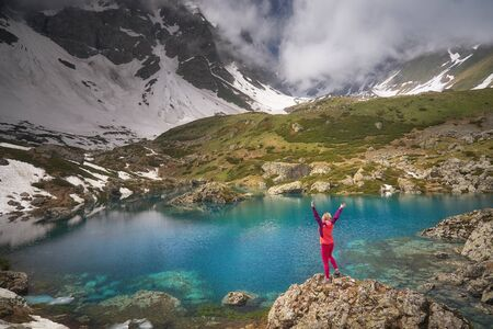 Hiking woman standing with rise up hands at beautiful lake in mountains.