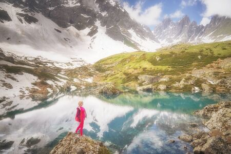 Hiking woman in red clothes stay at beautiful reflection of a lake in mountains.