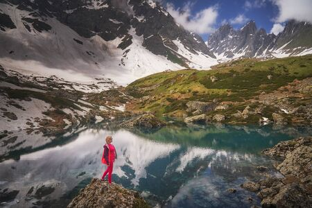 Hiking woman in red jacket stay at beautiful reflection of a lake in mountains.
