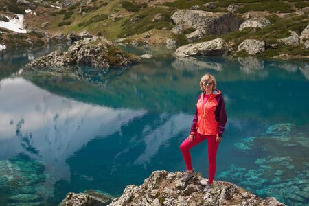 Hiking woman in red jacket stay at beautiful lake in mountains.