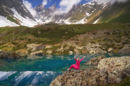 Hiking woman in red clothes sitting at beautiful turquoise lake in mountains.