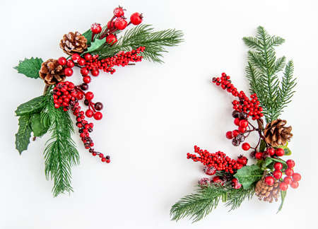 Green fir branches with red berries and Christmas decorations on a white background. Merry Christmas or Happy New Year concept. Flat lay, top view, copy space