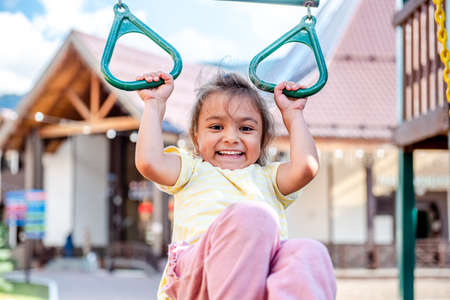 A little cheerful girl plays on vacation in the park on a children's playground. The child is engaged on gymnastic rings on the street on vacation. The child goes in for sports on simulators.
