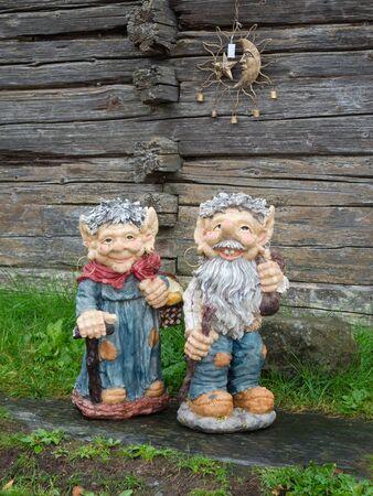 dunce cap: Cute elfs on green grass near old wooden wall