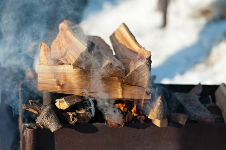 inflames smoking logs in the grill outdoors photo