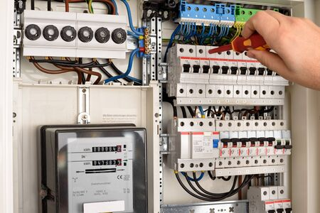 amp: An electrician is working on a fuse box
