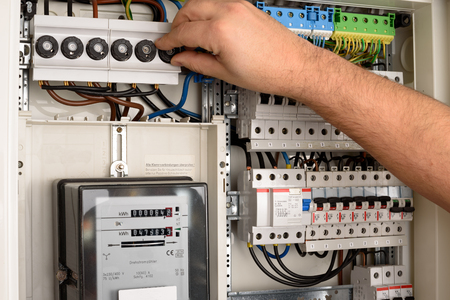An electrician is working on a fuse box