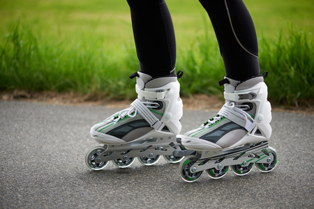 Close-up of female legs riding roller skates.
