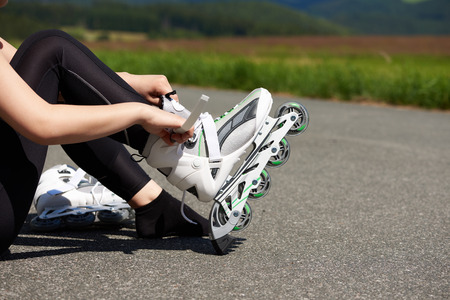 roller blade: Woman is going rollerblading. Putting on inline skates. Close up. Sport lifestyle.