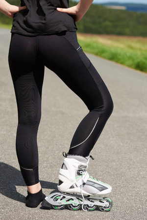 Close-up of a young woman with only one shoe roller skates. Back view. Stock Photo