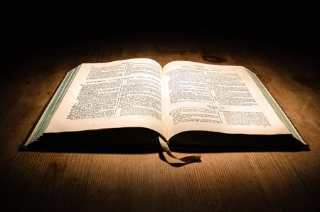 vangelo aperto: Vecchia bibbia su un tavolo di legno con uno sfondo scuro