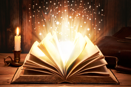 Old book with magic lights on wooden table by candlelight