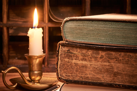 Old book on wooden table by candlelight Stok Fotoğraf