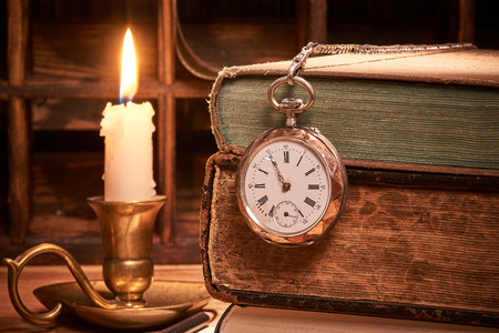 Old books with antique pocket watch by candlelight Stok Fotoğraf