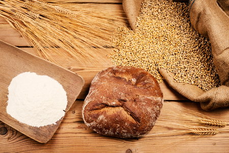 Bread with corn and wheat flour on wooden table Zdjęcie Seryjne
