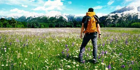 Mann mit Rucksack auf einer Blumenwiese genießt die Aussicht auf die Alpen