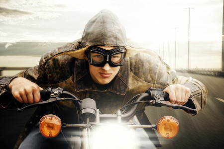 Young man with hat and goggles vintage look driving on a road Stock Photo