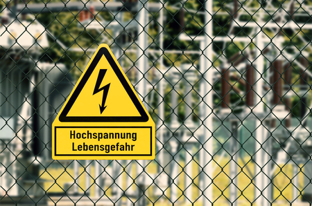 Electrical hazard sign placed on a fence of an electrical substation Stock Photo