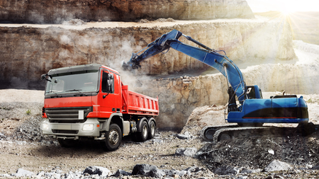 Excavator is loading a dump truck at the mine Stock Photo